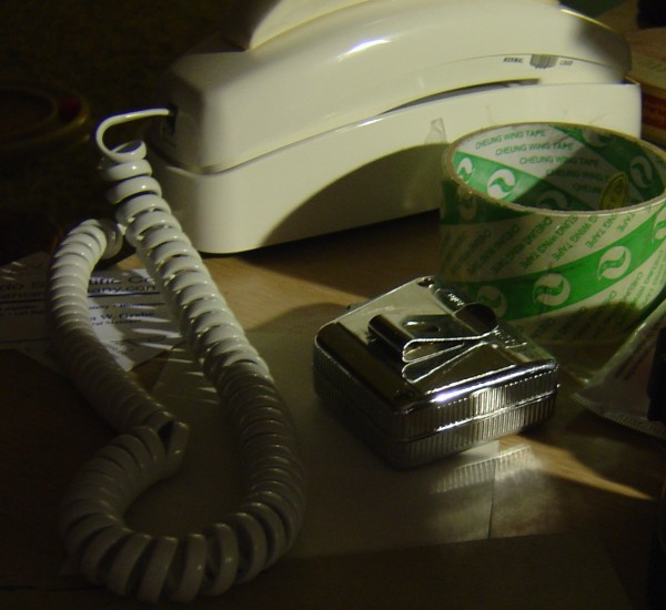 Photo showing tape measure, phone and tape on Cluttered desk