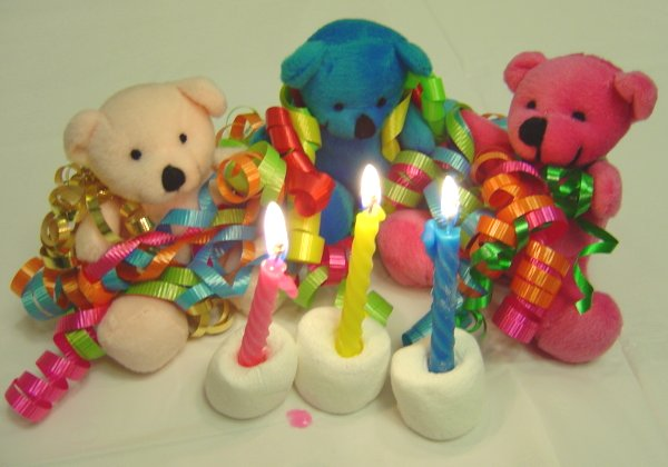 Photo of three teddy bears with colorful birthday ribbons and candles