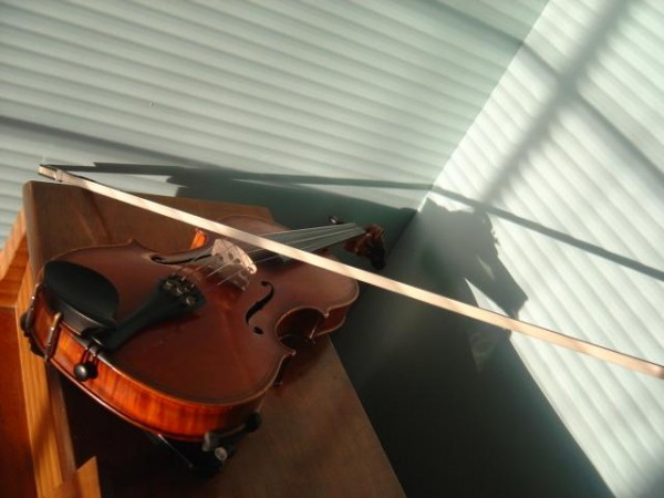 Photo of a violin with shadows from the window blinds