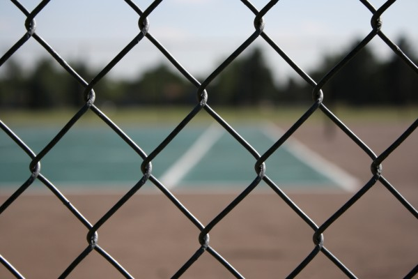 close up photo of chain link fence with tennis court in the background