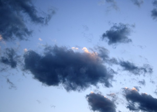 free photograph of dark wispy clouds in a blue sky