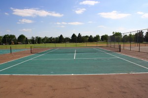 Free photo of a tennis court with grass, trees and blue sky in the background