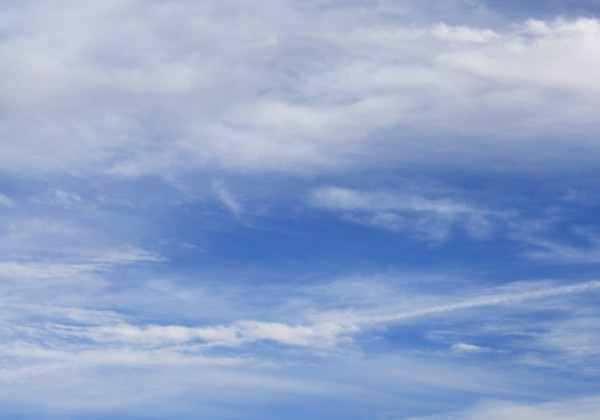 Free photograph of a blue sky with white clouds and a visible airplane trail