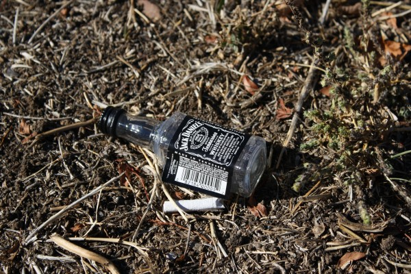 free photo of a Jack Daniels bottle tossed on the ground with cigarette butt