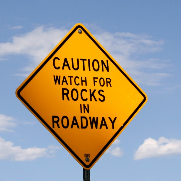 Caution Rocks in Roadway Sign - Free Photo